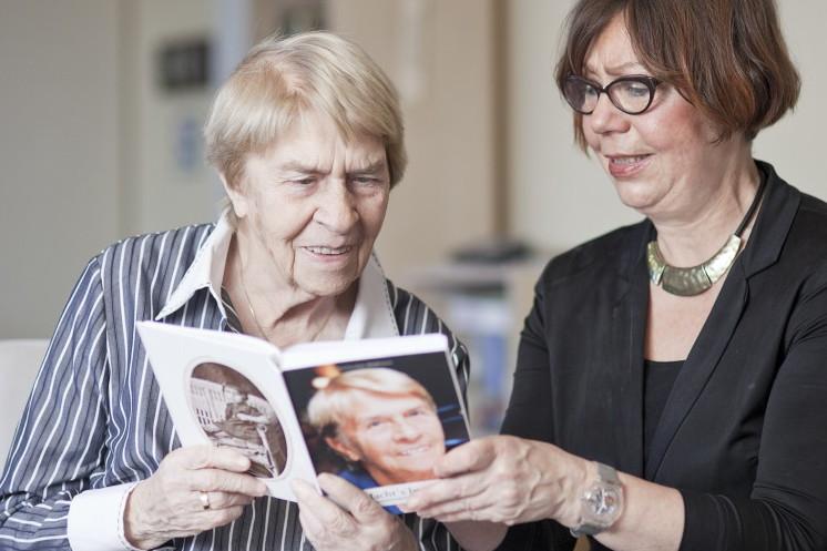 Die Biografinnen bei der Arbeit: Eine Kundin betrachtet ihr fertiges Lese-Buch zusammen mit Gislinde Schwarz.