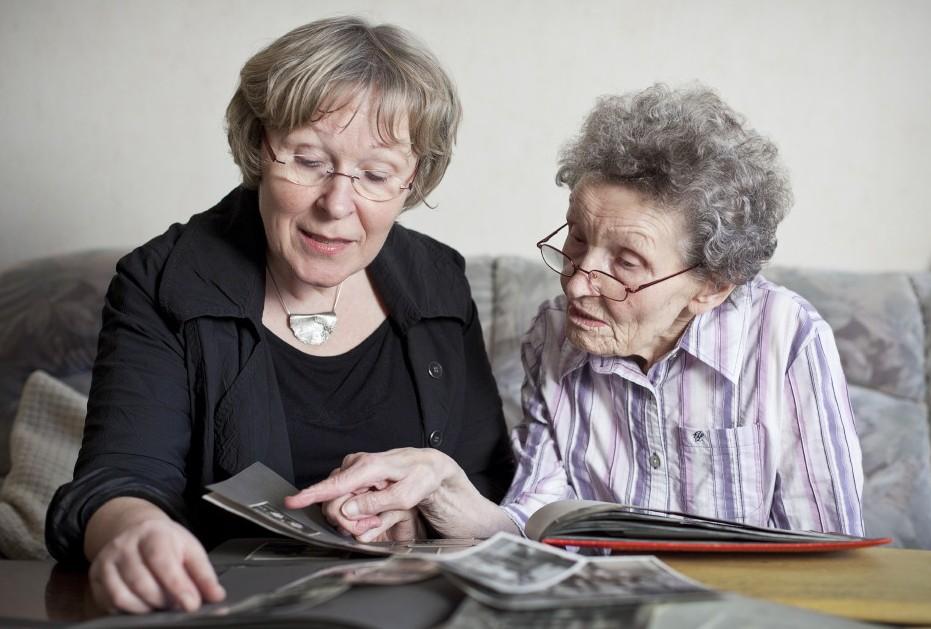 Die Biografinnen bei der Arbeit: Rosemarie Mieder und eine Kundin suchen in Fotoalben nach Lebenserinnerungen.