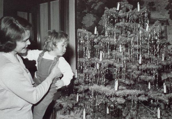 Weihnachten 1960er Jahre: Eine Mutter zeigt ihrer Zweijährigen den mit Lametta geschmückten Baum