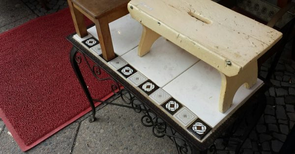 Tischchen aufgestapelt vor einem Trödelgeschäftdler