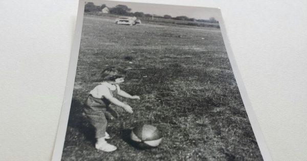 Lebenserinnerung an die 60iger Jahre: Mädchen spielt mit einem Ball auf einer großen Wiese, s/w-Foto